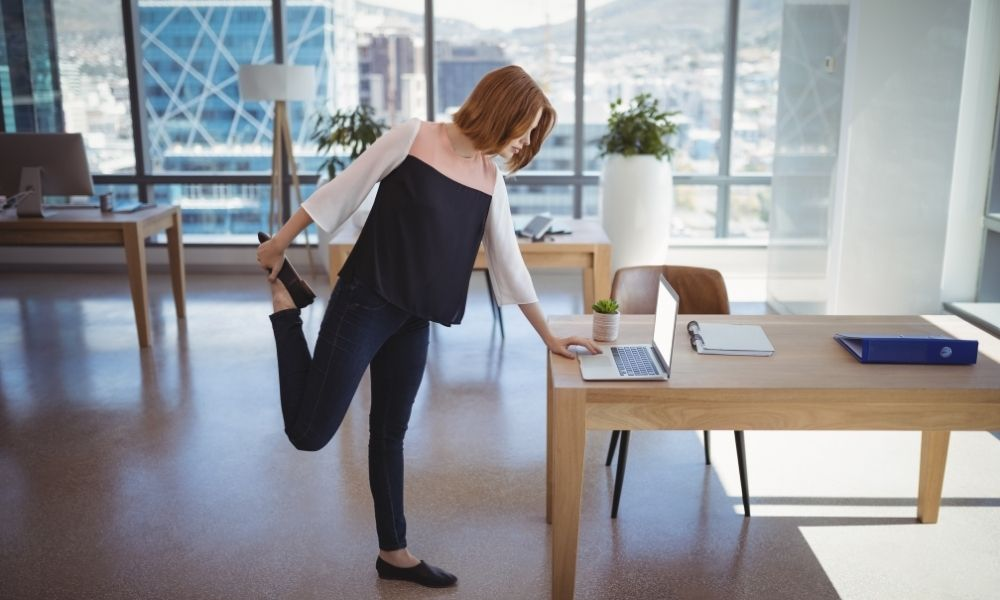 Woman performing a rear leg raise while working at her laptop
