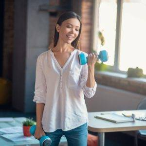 Young woman holding small dumbbell weights in office, fitness workout at office