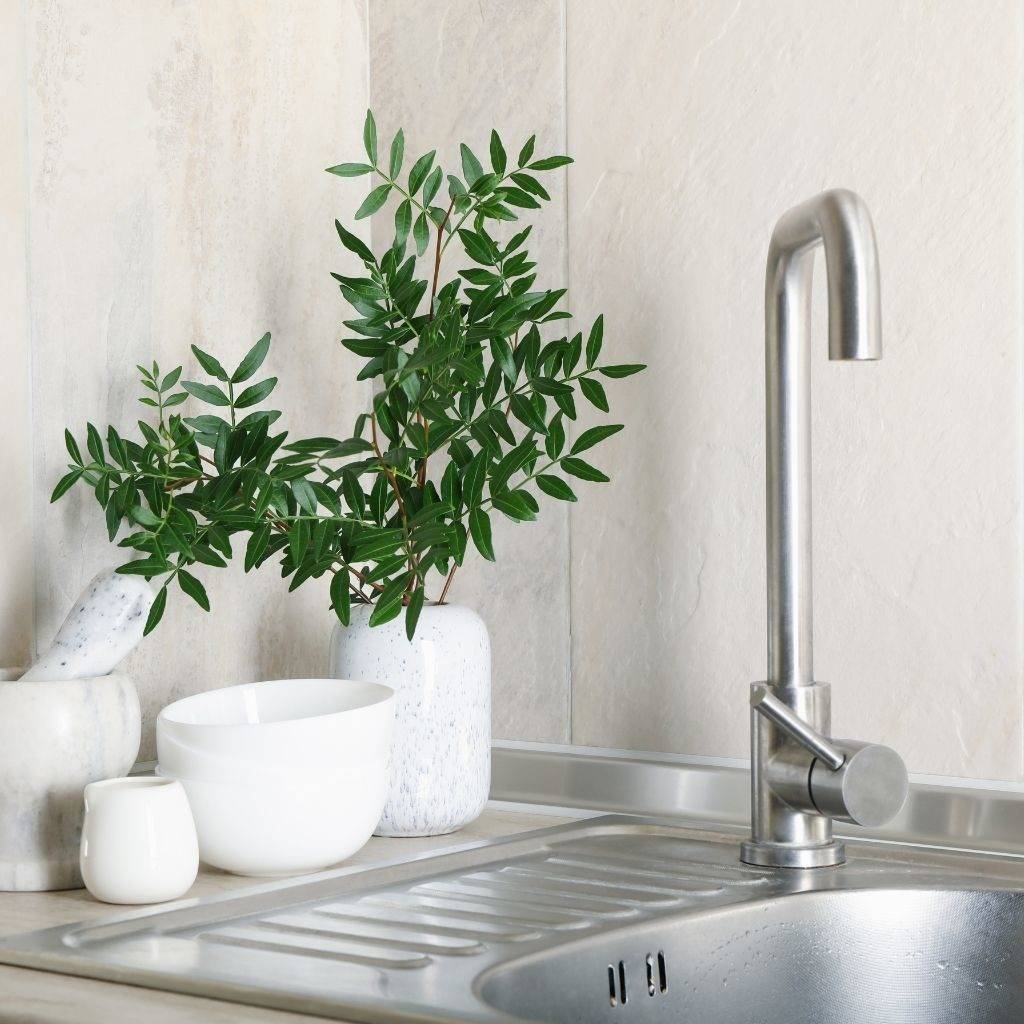Top mount stainless steel kitchen sink with white ceramic kitchen utensils and plants