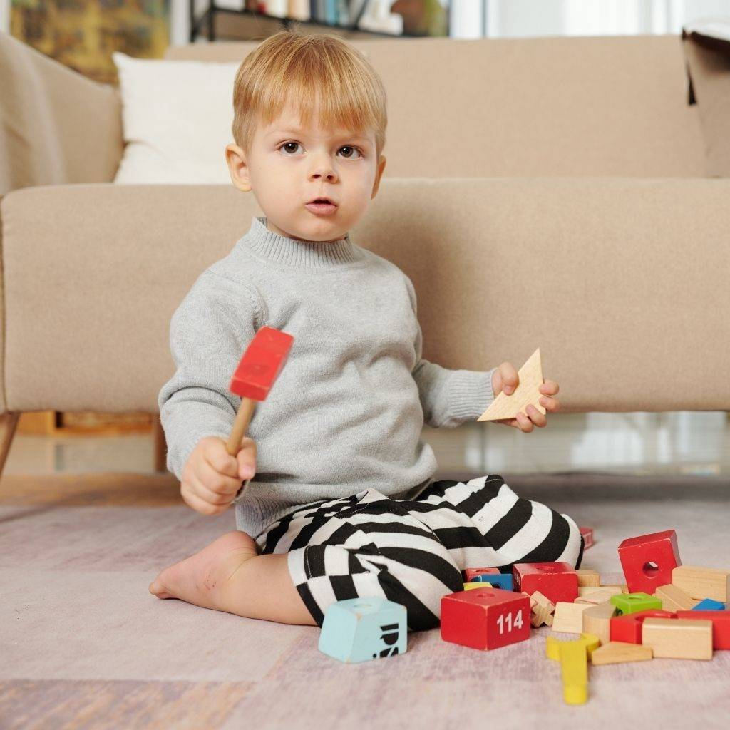 Toddler playing with wooden blocks on the floor